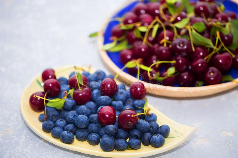 Delicious and fresh berries in summer. On the table are bowls of cherries and blueberries close-up royalty free stock photography