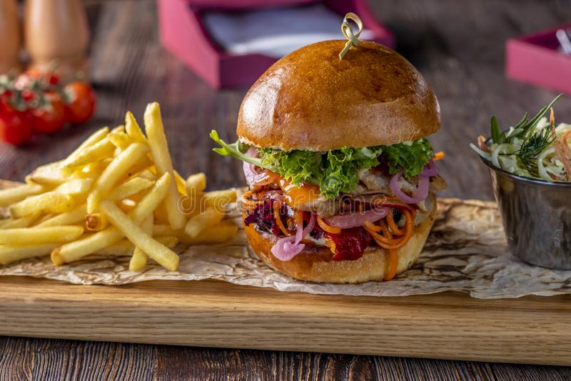 Delicious fresh burger with chicken, sauce and french fries on a wooden board, rustic style, fast food. Horizontal photo royalty free stock photos