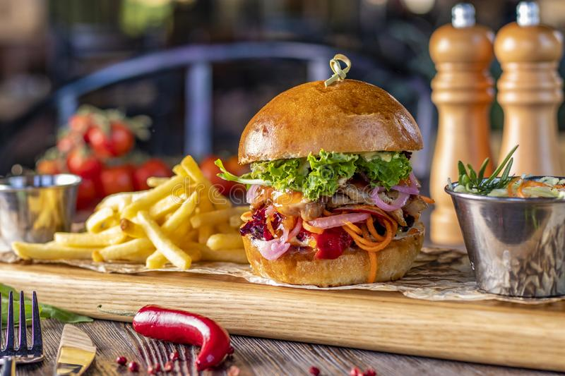 Delicious fresh burger with chicken, sauce and french fries on a wooden board, rustic style, fast food. Horizontal photo stock photos