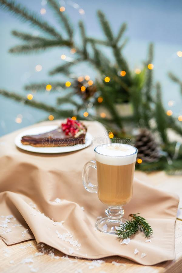 Delicious fresh festive morning cappuccino coffee in a glass cup and cupcake dessert on the wooden table, fireflies and spruce royalty free stock images