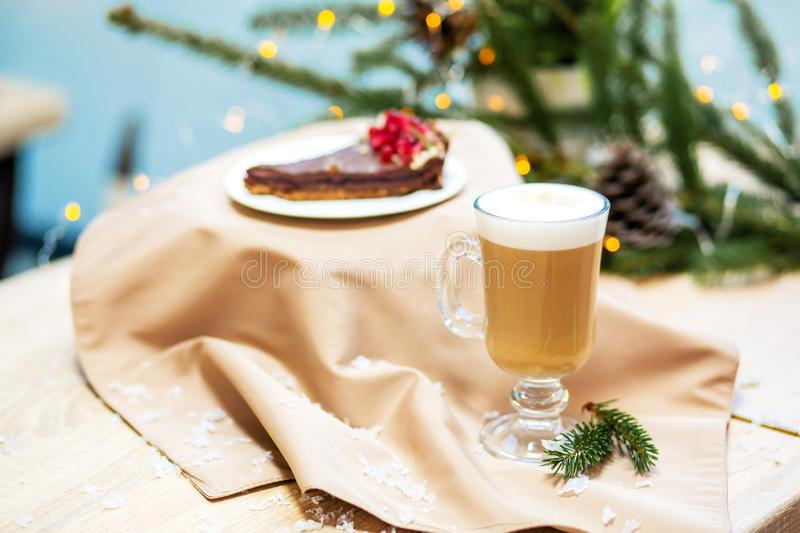 Delicious fresh festive morning cappuccino coffee in a glass cup and cupcake dessert on the wooden table, fireflies and spruce. Branches stock photography