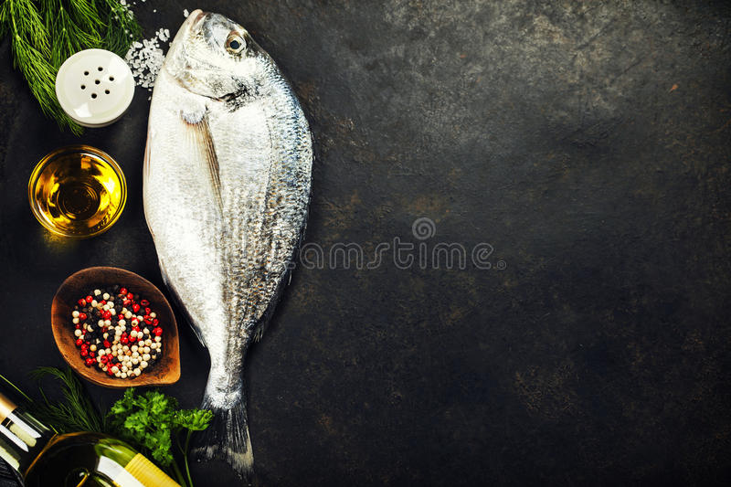Delicious fresh fish. On dark vintage background. Fish with aromatic herbs, spices and vegetables - healthy food, diet or cooking concept stock photography