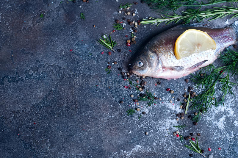 Delicious fresh fish on dark vintage background. Raw fresh river fish on plate cutting board. Top view, copy space stock image