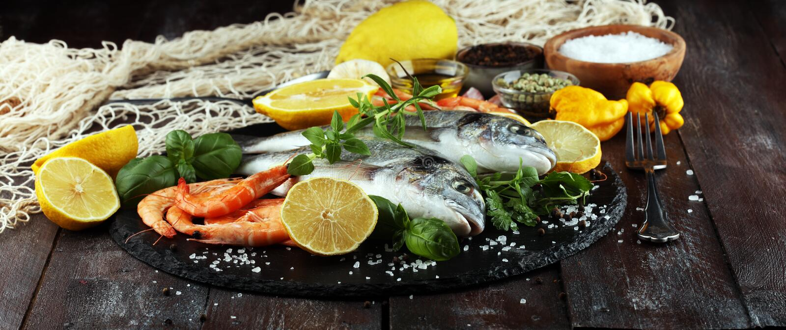 Delicious fresh fish. Fish with aromatic herbs, spices and vegetables - healthy food, diet or cooking concept. Delicious fresh fish. Fish with aromatic herbs stock image