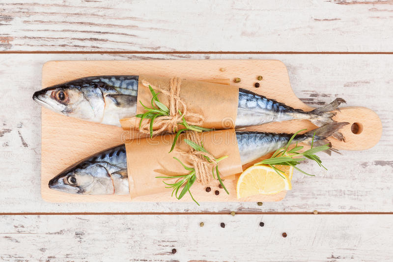 Delicious fresh fish. Delicious fresh mackerel fish on wooden kitchen board with lemon, rosemary and colorful peppercorns on white textured wooden background stock photography