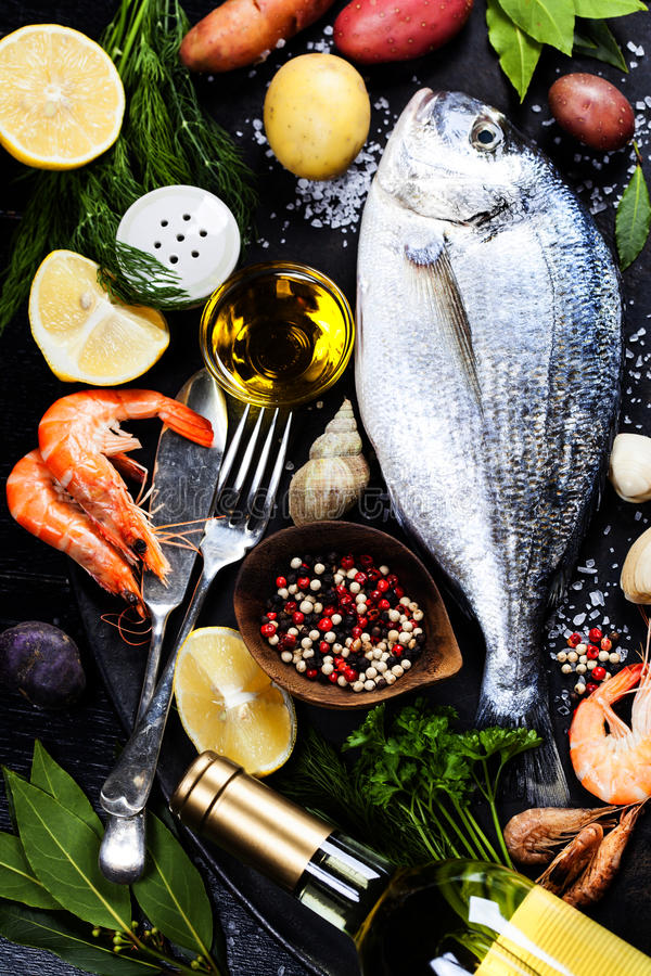 Delicious fresh fish. And seafood on dark vintage background. Fish, cockles and shrimps with aromatic herbs, spices and vegetables - healthy food, diet or stock photos