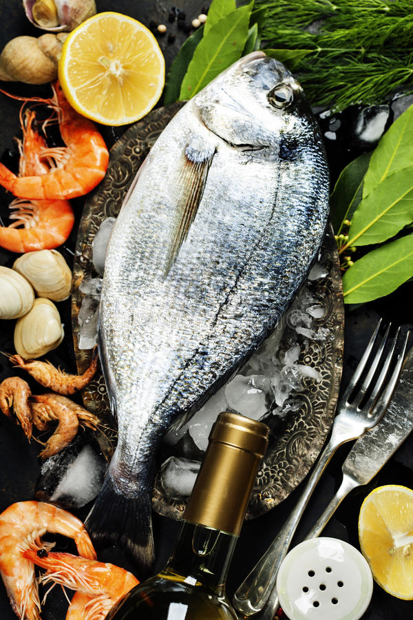 Delicious fresh fish. And seafood on dark vintage background. Fish, cockles and shrimps with aromatic herbs, spices and vegetables - healthy food, diet or royalty free stock images