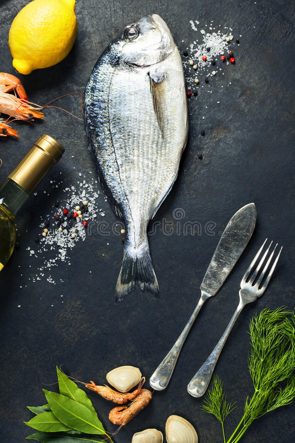 Delicious fresh fish. And seafood on dark vintage background. Fish, cockles and shrimps with aromatic herbs, spices and vegetables - healthy food, diet or royalty free stock photo