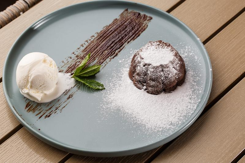 Delicious fresh fondant with hot chocolate and ice cream and mint served on plate. Lava cake recipe. Wooden background. stock photography