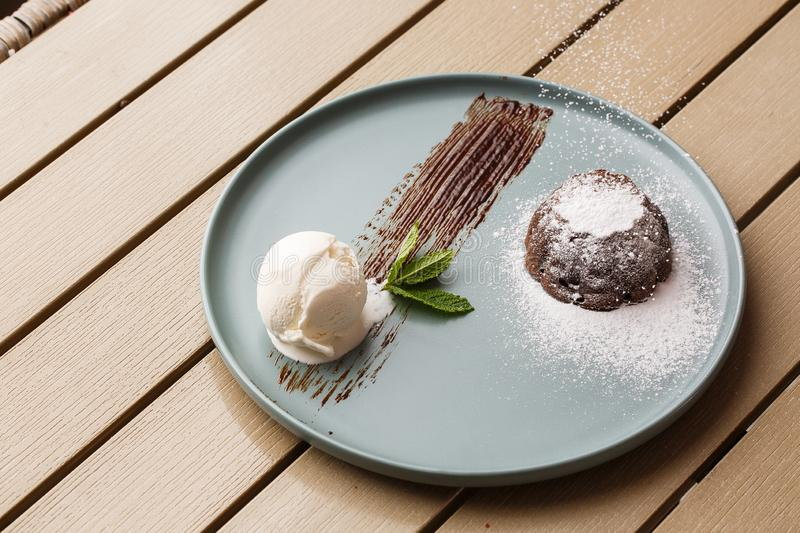 Delicious fresh fondant with hot chocolate and ice cream and mint served on plate. Lava cake recipe. Wooden background. royalty free stock photography