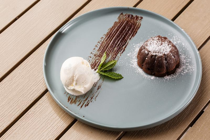 Delicious fresh fondant with hot chocolate and ice cream and mint served on plate. Lava cake recipe. Wooden background. stock image