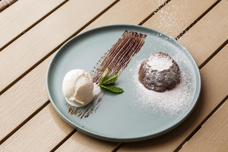Delicious fresh fondant with hot chocolate and ice cream and mint served on plate. Lava cake recipe. Wooden background. royalty free stock image