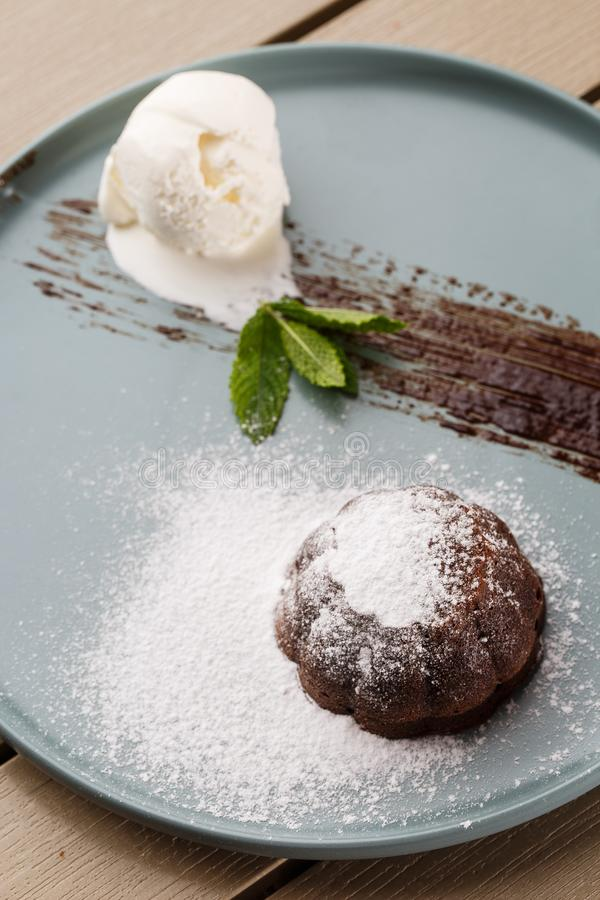 Delicious fresh fondant with hot chocolate and ice cream and mint served on plate. Lava cake recipe. Wooden background. royalty free stock photo