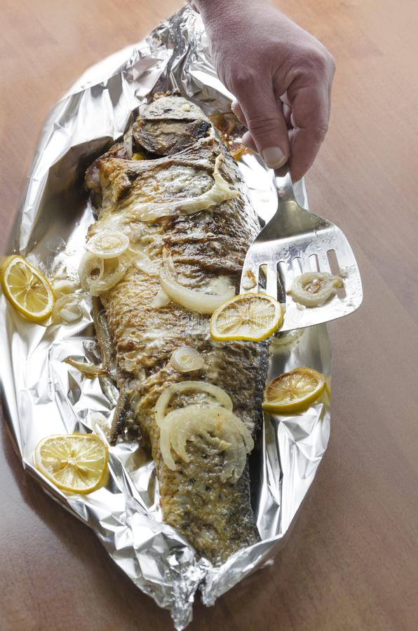 Delicious fresh grilled carp fish with slices of lemon.Chef using spatula to put slice of lemon on roasted fish.Vertical shot royalty free stock photos