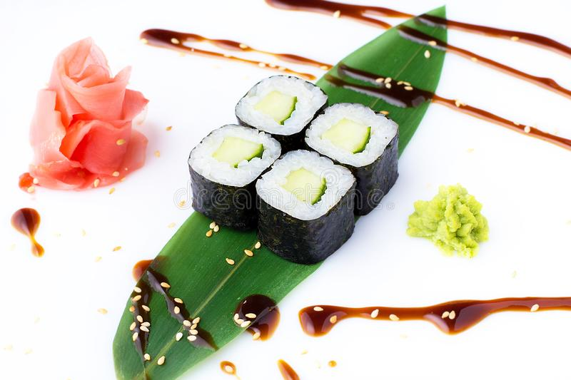 Delicious fresh mini-rolls with cucumber on a banana leaf. Sushi rolls on a white background with ginger and wasabi. The Japanese stock images