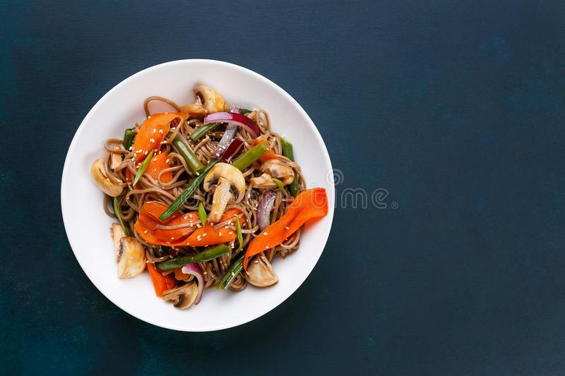 Delicious fresh pad thai noodles with mushrooms and vegetable sl. Ices on dark background, flat lay with copy space. Thai food, vegetarian meals stock images
