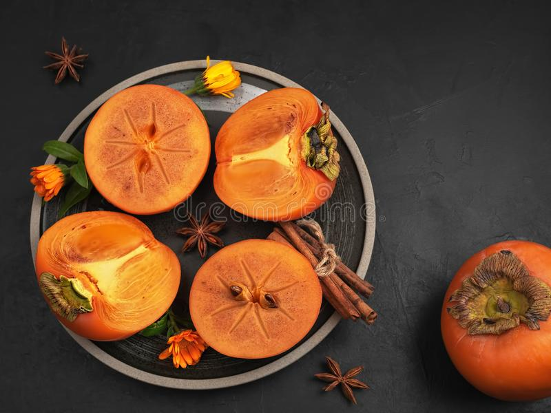 Delicious fresh persimmon fruit on a black background. Persimmon slices on a black plate. top view. Ingredients and spices for royalty free stock photos