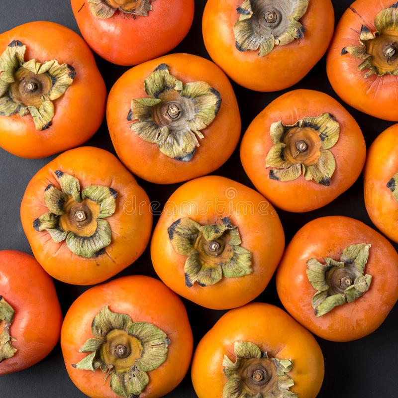 Delicious fresh persimmon fruits on black background stock photography
