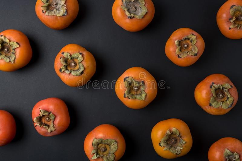Delicious fresh persimmon fruits on black background royalty free stock photos