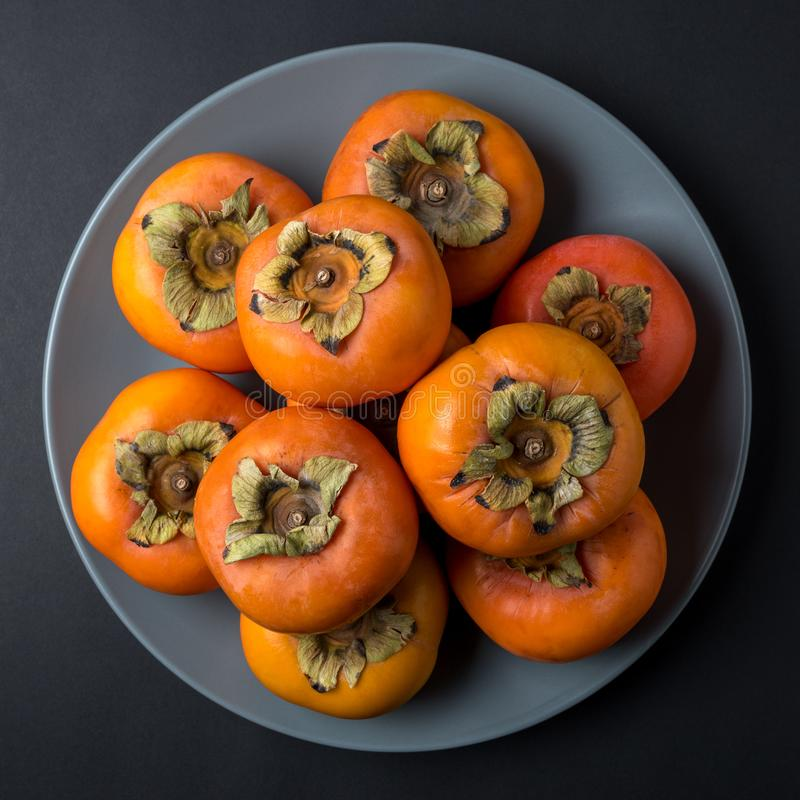 Delicious fresh persimmon fruits on black background stock images