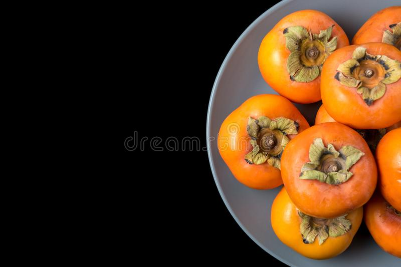 Delicious fresh persimmon fruits on black background stock image