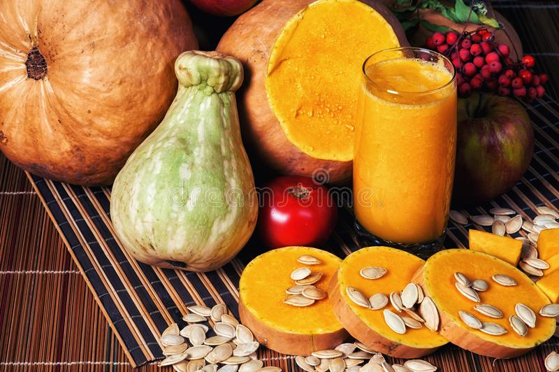 Delicious fresh pumpkin juice with the seeds in the Studio on wooden background. Smoothies on Halloween royalty free stock image
