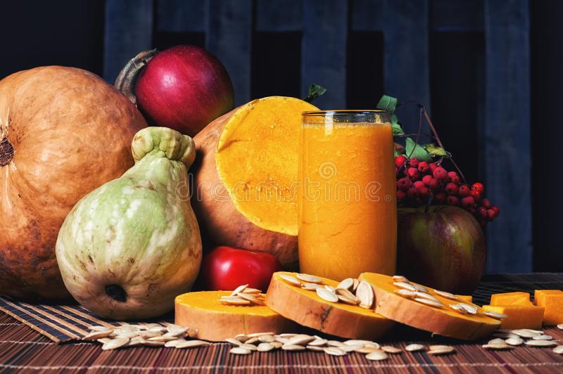 Delicious fresh pumpkin juice with the seeds in the Studio on wooden background. Smoothies on Halloween stock image