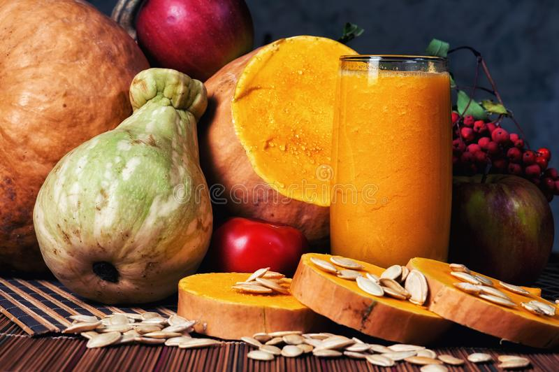 Delicious fresh pumpkin juice with the seeds in the Studio on wooden background. Smoothies on Halloween stock photo