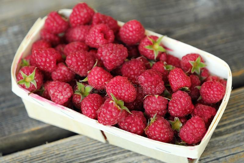 Delicious fresh raspberry in the wooden basket stock photo