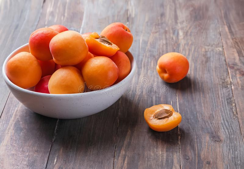 Delicious fresh ripe apricots in a bowl on the wooden table. Close-up stock photo