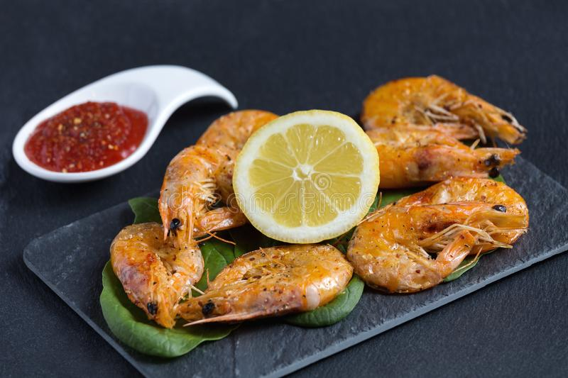 Delicious fresh shrimps cooked, sauteed, with spicy tomato sauce, butter and lime on, served on a black fancy plate. Negative spac. E. Copy space for text. Close stock photo