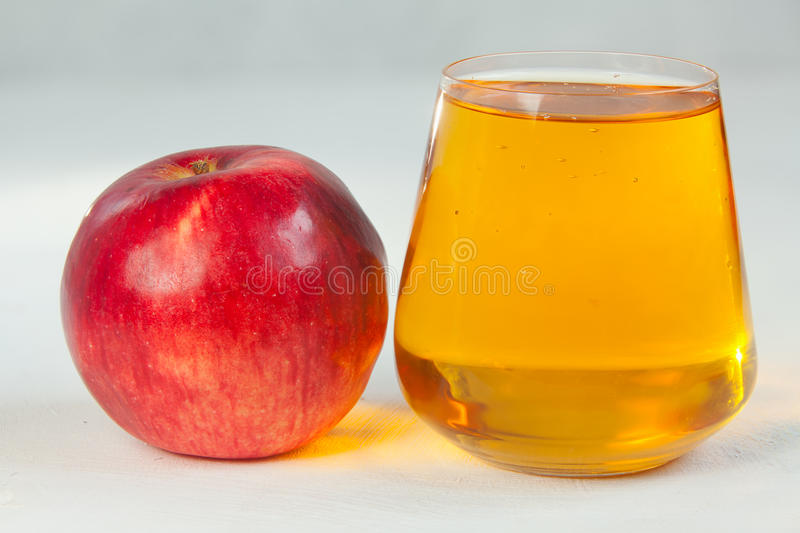 Delicious fresh squeezed apple juice in transparent glass royalty free stock photos