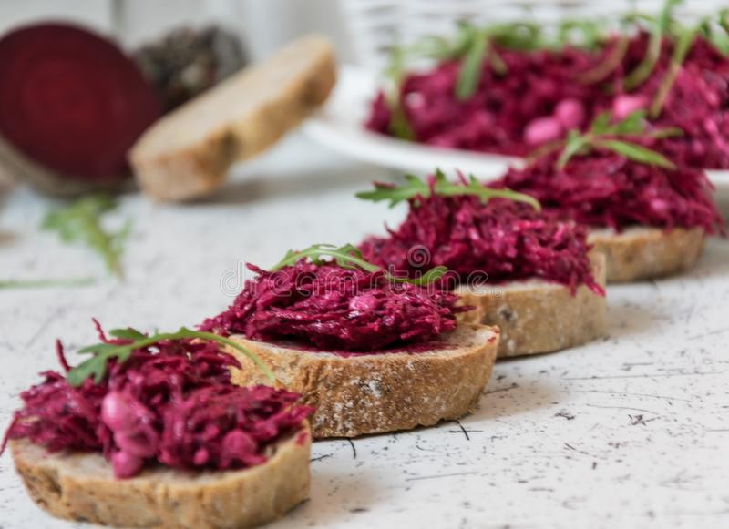 Tzatziky from red beet and cottage cheese. Decorated with fresh arugula royalty free stock photography