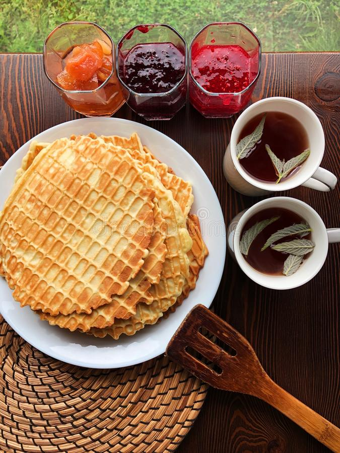 Delicious fresh waffles and jam on the table stock photo