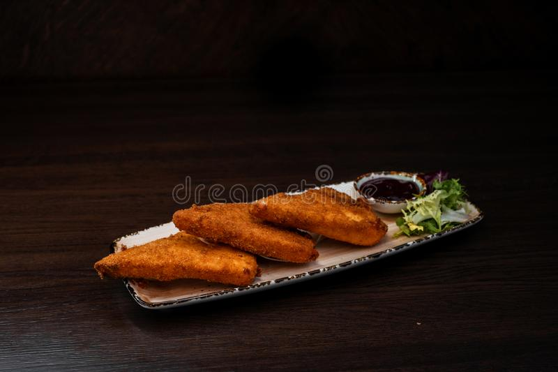 Delicious fried chicken breaded nuggets with ketchup decorated with greens on a plate in a restaurant. Fast tasty food. royalty free stock photography