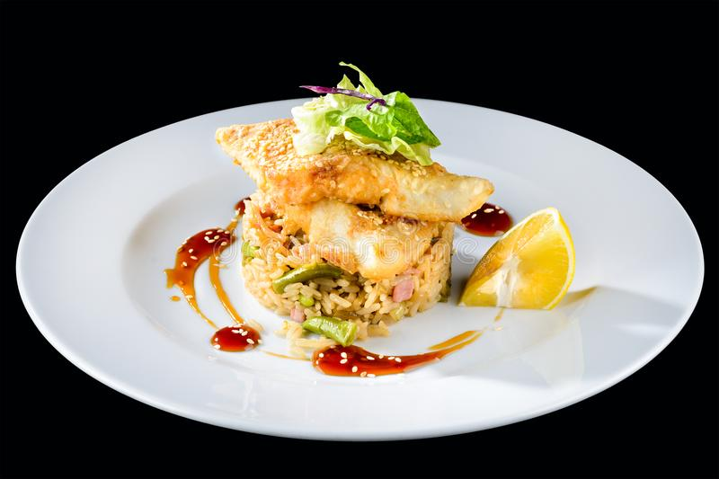 Delicious fried cod fillet with risotto, salad and lemon in a white plate isolated on dark background royalty free stock photos