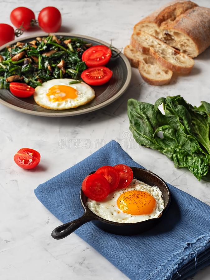 Delicious fried eggs in a pan with fried spinach and mushrooms located on a gray table. Close-up. Vertical orientation stock photo
