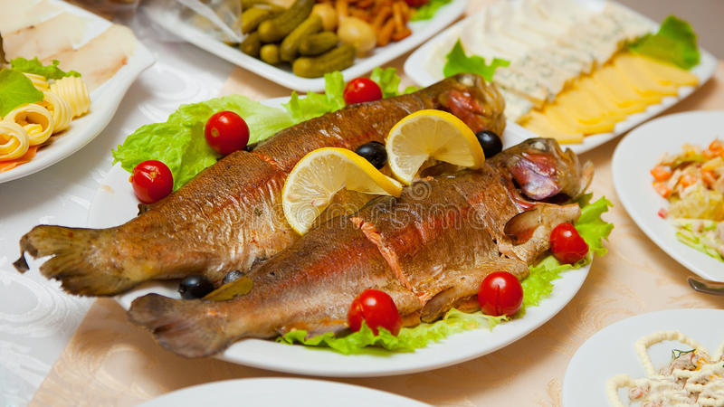 Delicious fried fish on table. Dish of delicious fried fish on the table stock photos