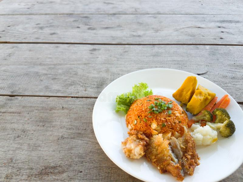 Fried rice, fried chicken  vegetables on a wooden table royalty free stock images