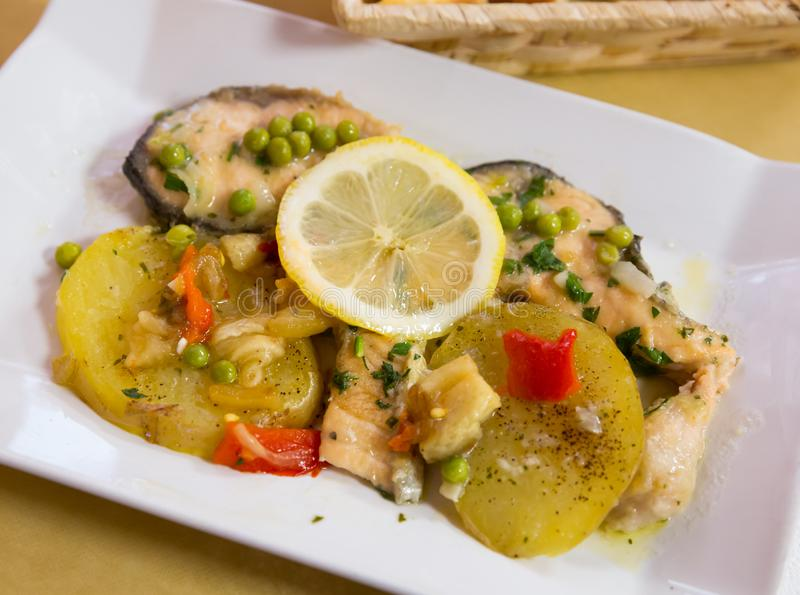 Delicious fried salmon fillets served with lemon, potato, bell peppers and greens peas stock photography