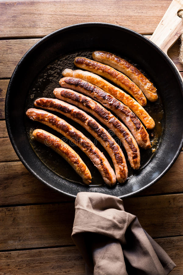 Delicious fried sausages with golden crust in iron cast pan, linen towel, top view royalty free stock photography