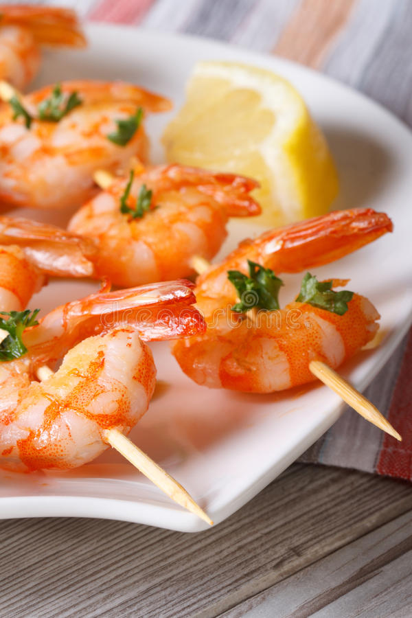 Delicious fried shrimp on wooden skewers macro. Vertical royalty free stock photo