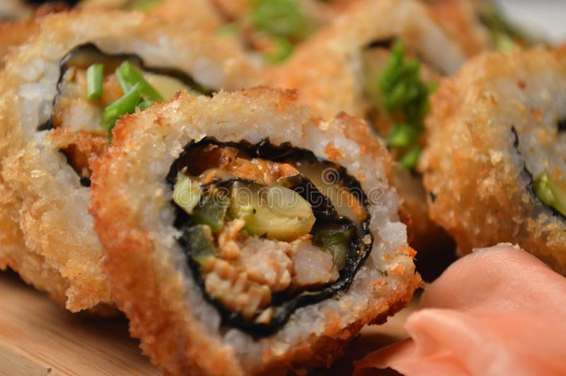 Delicious fried sushi served in a wooden board royalty free stock photos