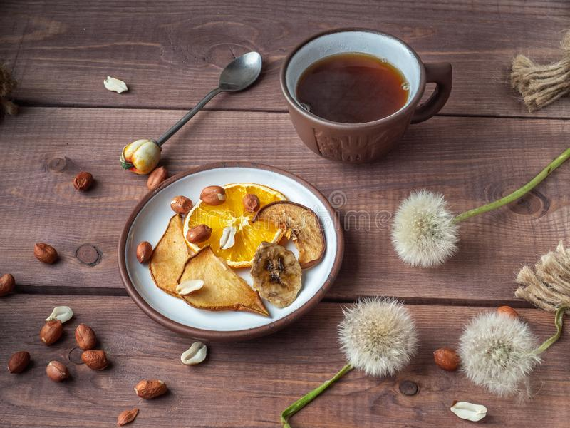 Delicious fruit chips and peanut nuts for fitness girls with a cup of coffee royalty free stock photos