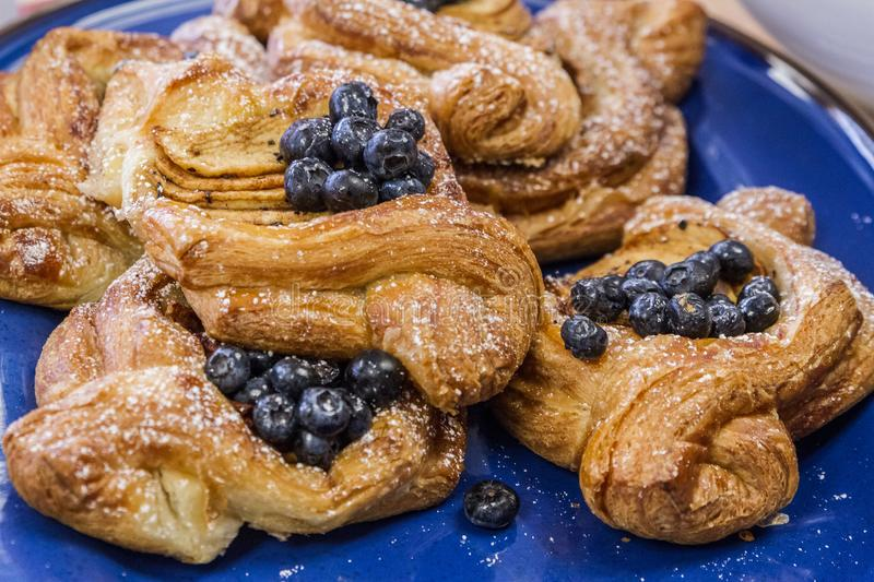 Delicious Fruit Danish Pastries. A blue plate holding beautiful and decadent apple and blueberry Danish pastries stock photos