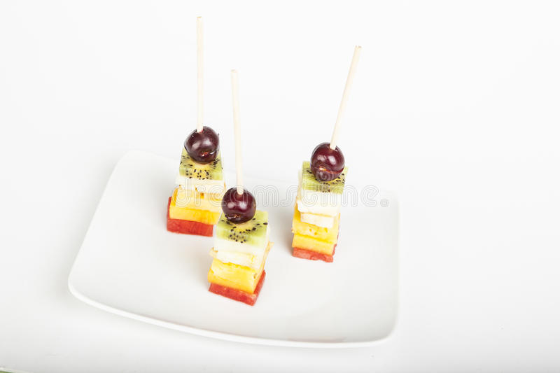 Delicious fruit kabobs over white stock images