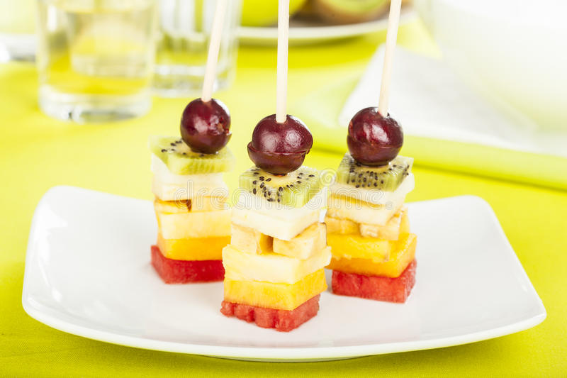Delicious fruit skewers served on a plate stock image