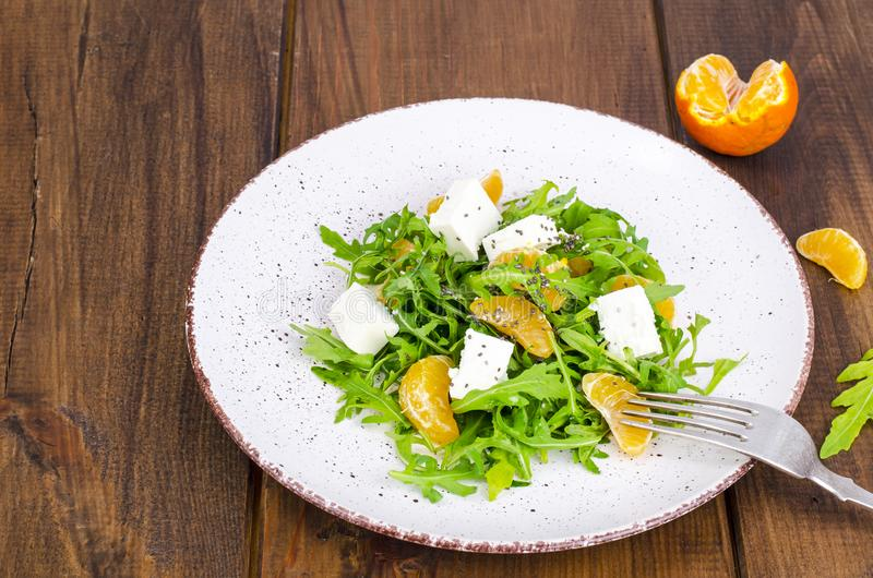 Delicious fruit and vegetables salad. Tangerine, feta cheese, arugula and chia seeds in plate. Healthy food concept. Studio Photo royalty free stock photos