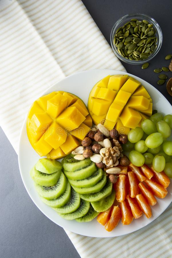 Delicious fruits platte isolated. Mango, kiwi, citrus, nuts, grapes. Mix of various exotic fruits. Healthy fruit salad, healthy stock images