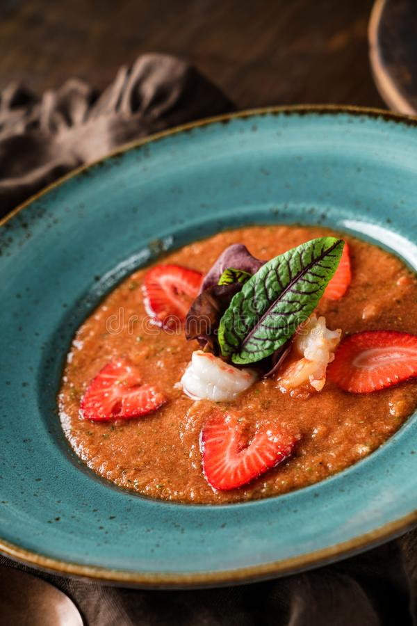 Delicious gazpacho soup with shrimps, strawberries and cucumber in bowl over brown wooden background. Healthy food, clean eating stock photos